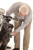 Elderly man check motorcycle — Stock Photo