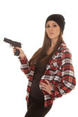 Woman in beanie and plaid shirt gun point side — Zdjęcie stockowe