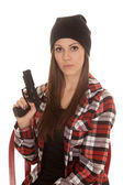 Woman in beanie and plaid shirt gun serious — Stock Photo
