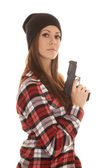 Woman in beanie and plaid shirt gun side serious — Zdjęcie stockowe