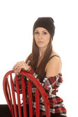 Woman in beanie and plaid shirt sit red chair — Zdjęcie stockowe