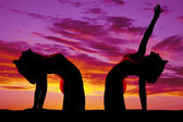 Silhouette of woman doing yoga bend back reach up — Stockfoto