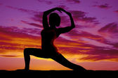 Silhouette yoga woman lunge head between arms — Stock Photo