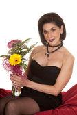 Woman black dress sit on red sheet flower smile — Stock Photo