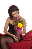 Woman black dress sit on red sheet smell flower — Stock Photo