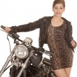 Stock Photo: Womleopard print dress stand by motorcycle