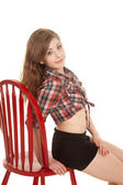 Cowgirl plaid shirt red chair side sit — Stockfoto