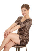 Woman leopard dress cross legs hands knees — Stock Photo