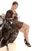 Woman leopard dress motorcycle lean smile legs — Stock Photo