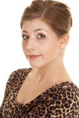 Woman leopard print dress sit close small smile — Stock Photo