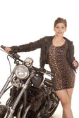 Woman leopard print dress stand by motorcycle — Stock Photo