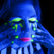 Woman black light eyes closed hands on face — Stock Photo