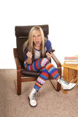 Woman colorful pants sit with remote excited — Stock Photo