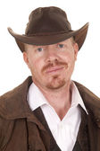 Cowboy leather coat hat smirk close — Stock fotografie
