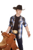 Cowboy holding a saddle — Stock Photo