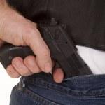 Постер, плакат: Pull gun out of pants close