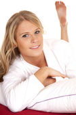 Woman white robe red sheet lay looking — Stock Photo