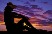 Silhouette woman sun hat sit hands on knees — Stock Photo