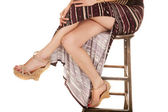 Woman legs sit in slit skirt — Stock Photo