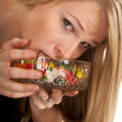 Woman eating jellybeans mouth in bowl — Stock Photo #45718793