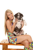 Woman colorful dress sit hold dog up smiling — Stock Photo