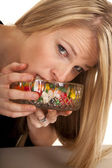Woman eating jellybeans mouth in bowl — Stock Photo