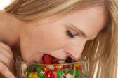 Woman eating jellybeans tongue in bowl eyes closed — Stock Photo