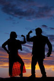 Silhouette man woman facing each other both flex one arm — Stock Photo