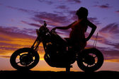 Silhouette pregnant woman on motorcycle. — Stock Photo