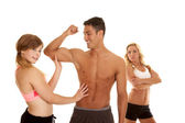 Fitness man with two women one mad arms folded — Stock Photo