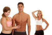 Fitness man with two women one touch abs — Photo