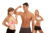 Fitness man with two women one touch muscle — Zdjęcie stockowe