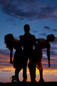 Silhouette man hold two women leaning back sunset — Stock Photo