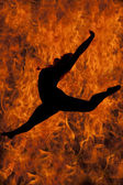 Silhouette of woman dancing jump in fire — Stock Photo