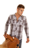 Man plaid shirt holding saddle look to side — Stock Photo