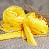 Heap of pasta tagliatelle and noodles on the sacking background — Stock Photo