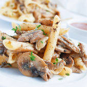 Pasta penne with mushrooms grilled in sour cream sauce — Stock Photo