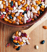 Full bowl of different haricot beans on the wooden table — Stock Photo