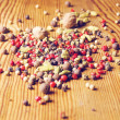 Different pepper seeds and cardamom on the wooden table — Stock Photo
