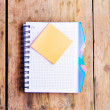Notepad and notepaper on the wooden background — Stock Photo