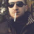 Stock Photo: Portrait of a stylish young man smoking outdoors