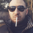 Portrait of a stylish young man smoking outdoors — Stock Photo