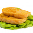 Fried bread served on green salad leaves — Stock Photo