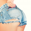 Sexy woman in jeans shorts with condom in back pocket — Stock Photo