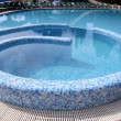 Curved blue tiled hotel resort swimming pool — Stock Photo
