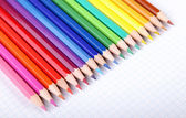 Multicolored crayons on white squared paper background. — Stock Photo