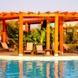 Stock Photo: Resort swimming pool, wood pergoland deck chairs