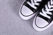 Black canvas sneakers on grey textile background — Stock Photo