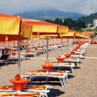 Sunchairs and umbrellas on Mediterranean beach — Stock Photo