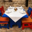 Italian outdoor restaurant with red and blue table and chairs — Stock Photo #13702843